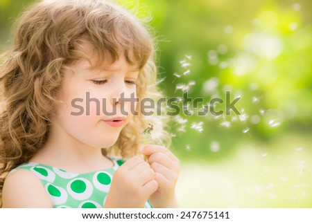 Beautiful child with dandelion flower in spring park. Happy kid having fun outdoors against green bokeh - stock photo