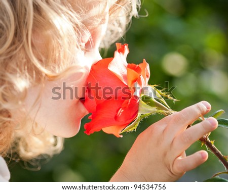 Beautiful child with flower against spring green background. Ecology concept - stock photo