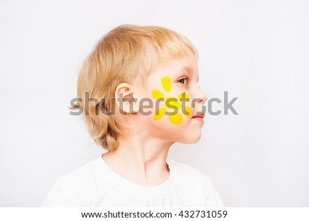 Beautiful child with hands in paint. Portrait of cute emotional kid. Close up of cheerful funny boy isolated on white background. Profile of blond caucasian baby with painted yellow sun on cheek. - stock photo