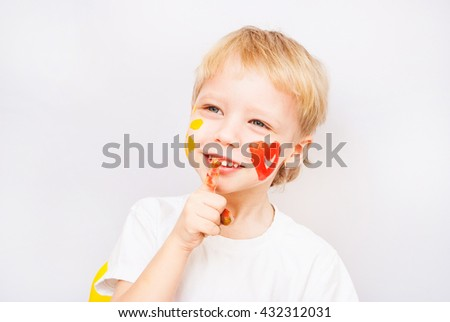 Beautiful child with hands in paint. Portrait of laughing emotional kid. Close up of cheerful funny boy isolated on white background. Baby with red heart and yellow sun on cheeks. Positive emotions. - stock photo