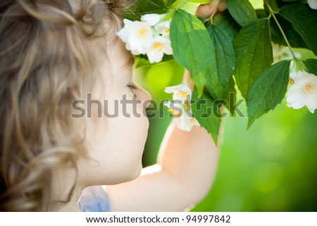 Beautiful child with jasmin flower against spring green background. Ecology concept - stock photo