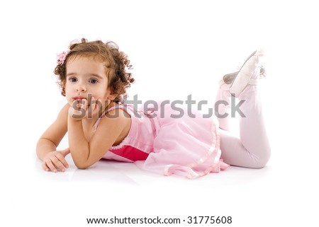 Beautiful Child with pink dress, lying on the floor .