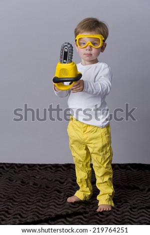 beautiful child with protective glasses and chain saw - stock photo