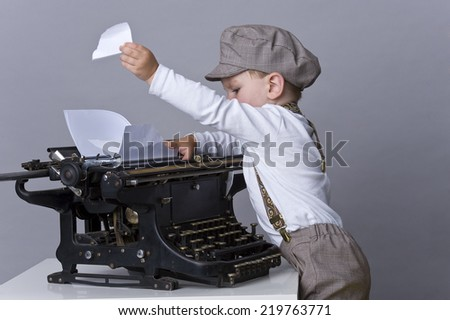 beautiful child with typewriter - stock photo