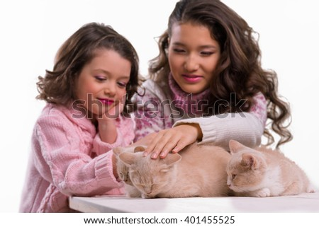 Beautiful children caress cats with love and smiles. Asian and Caucasian appearance of a girl and a kid in rosy clothes. White background. - stock photo