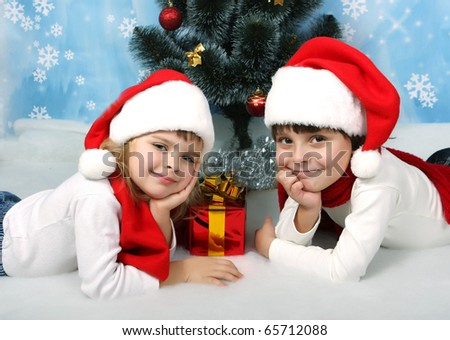 beautiful children in New caps lie under the tree