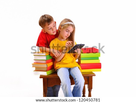 Beautiful children read e-book surrounded by several books isolate on white background - stock photo