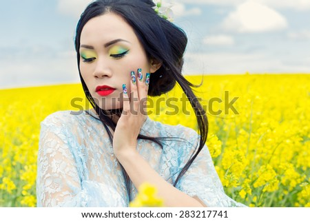 beautiful Chinese girl in kimono with long false nails with red lipstick in rape - stock photo