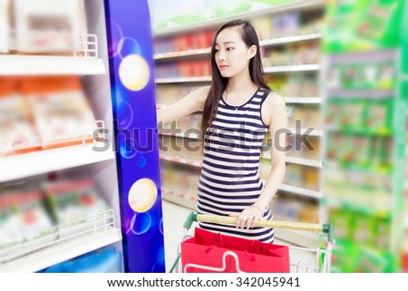 beautiful chinese girl, in the shopping center supermarket, buy her favorite fruits and vegetables