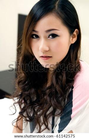 Beautiful chinese girl smiling indoors - stock photo