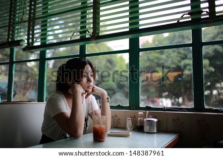 Beautiful chinese Girl waiting someone so long and feeling bad, She rested her chin on her hand in hong kong china - stock photo