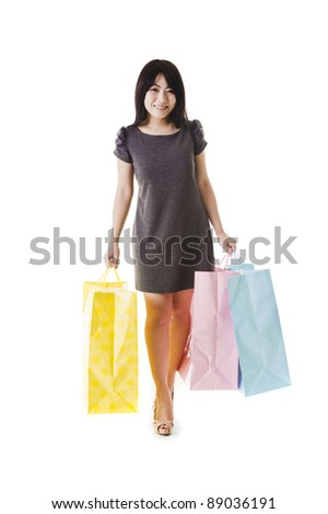 Beautiful Chinese woman with shopping bags in front of a white background. - stock photo