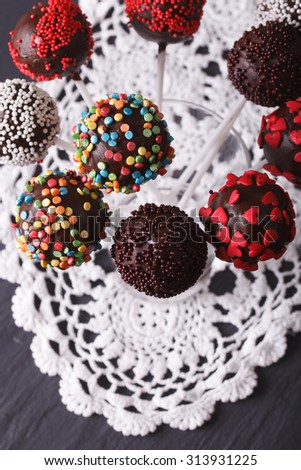 Beautiful chocolate cake pops with candy sprinkles close-up on a lace doily. vertical top view - stock photo