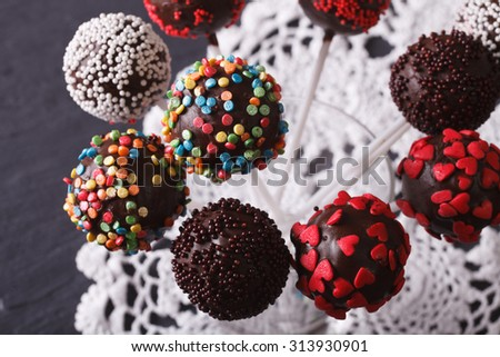 Beautiful chocolate cake pops with candy sprinkles close-up on the table. Horizontal top view - stock photo
