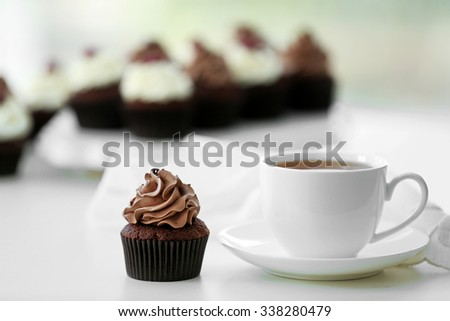 Beautiful chocolate cupcakes and cup of tea,  on table - stock photo