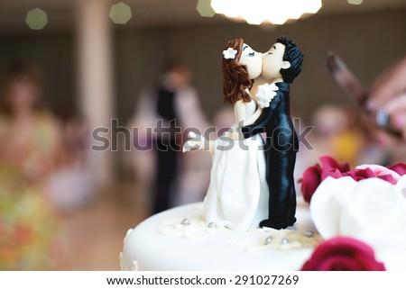Beautiful chocolate figurines on top of wedding cake. - stock photo