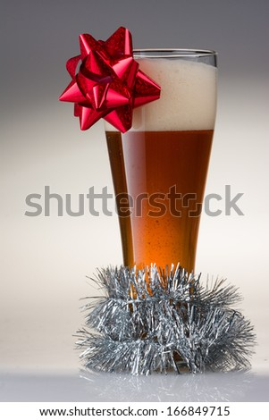 Beautiful Christmas Amber Beer with a Red Bow and Garland - stock photo