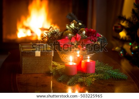 Beautiful Christmas background  with burning candles and fireplace at Christmas night