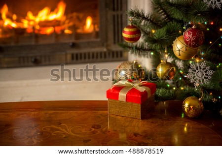 Beautiful Christmas background with present, Christmas tree and burning fireplace. Place for text