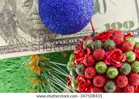 Beautiful Christmas ball in the shape of a bouquet and a hundred dollar bill hanging on the Christmas tree - stock photo
