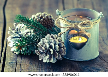 Beautiful Christmas decoration with a shabby chic tin lantern and pine cones with added retro vintage style filter - stock photo