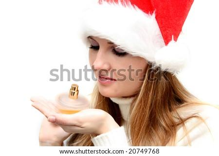 Beautiful christmas girl in santa hat holding bottle of perfume - stock photo