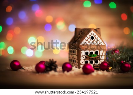 beautiful Christmas house with fir paws on wooden background - stock photo