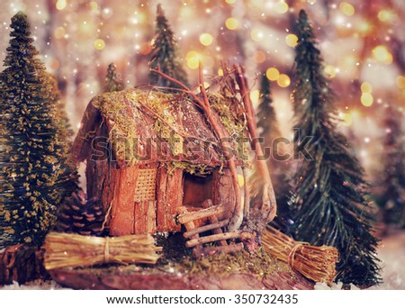 Beautiful Christmas still life, cute little wooden house surrounded by small pine trees, vintage style greeting card for New Year