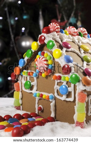 Beautiful Christmas table setting in front of Christmas Tree, featuring a gingerbread house made with frosting and candy sweets. - stock photo