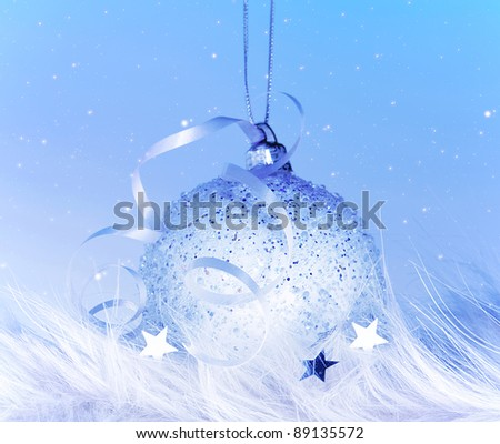 Beautiful Christmas tree decoration, silver blue ball over cold snow background - stock photo