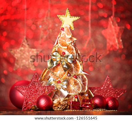 beautiful christmas tree of dry lemons with decor, on red background - stock photo