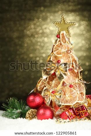 beautiful christmas tree of dry lemons with decor, on shine background - stock photo