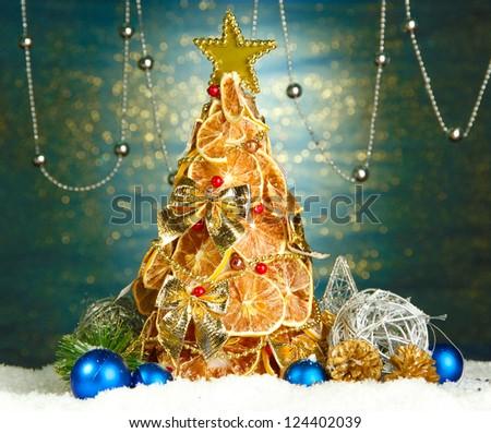 beautiful christmas tree of dry lemons with decor, on shine blue background - stock photo