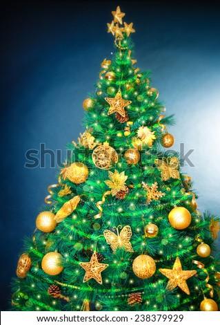 Beautiful Christmas tree over blue background, luxury golden decoration, traditional symbol of Christmastime holidays - stock photo