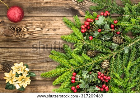 Beautiful christmas tree twigs of spruce and Christmas ornaments arranged on rustic wood background useful as christmas background in vintage style. - stock photo