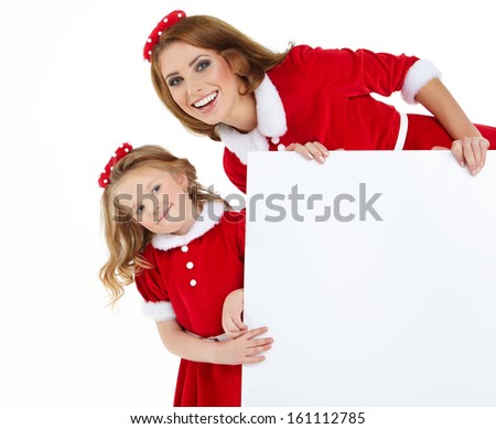 Beautiful christmas woman and little girl  in santa hat holding empty board  - stock photo