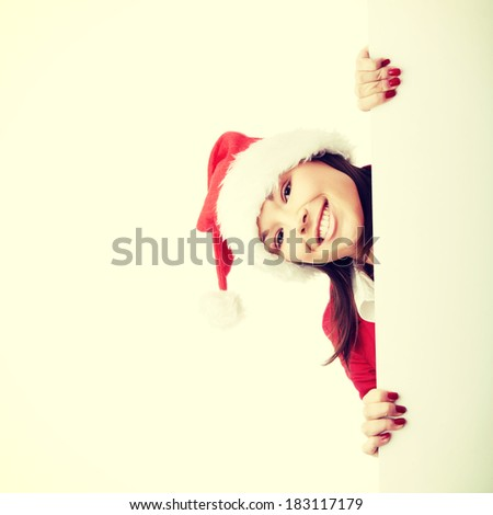 Beautiful christmas woman in santa hat holding empty board  - stock photo