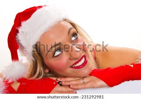 Beautiful christmas woman in santa hat holding empty board  - stock photo