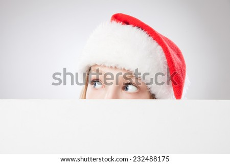 Beautiful christmas woman in santa hat holding empty board and looking to the left isolated on white background - stock photo