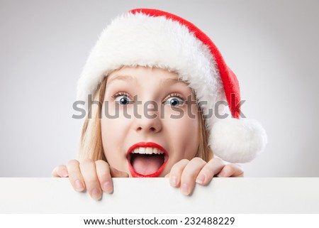 Beautiful christmas woman in santa hat holding empty board isolated on white background - stock photo