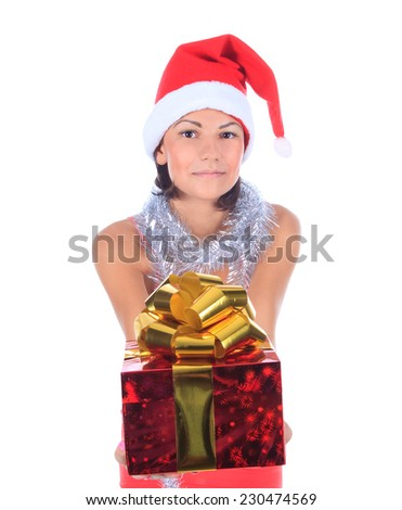 Beautiful christmas woman in santa hat holding gift - stock photo