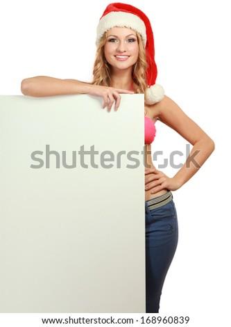 Beautiful christmas woman in santa hat near empty board - stock photo