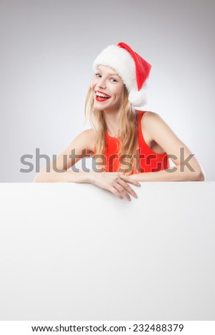 Beautiful christmas woman in santa hat pointing empty board, isolated on white background - stock photo