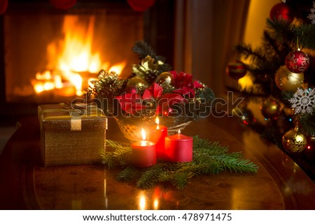 Beautiful Christmas wreath with red candles in living room with burning fireplace