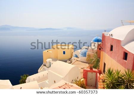 Beautiful church in Oia village overlooks caldera surrounding island of Santorini Greece - stock photo