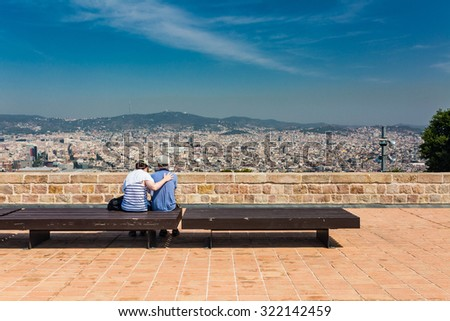 Beautiful city landscape in Barcelona and unidentified couple in summer time - stock photo