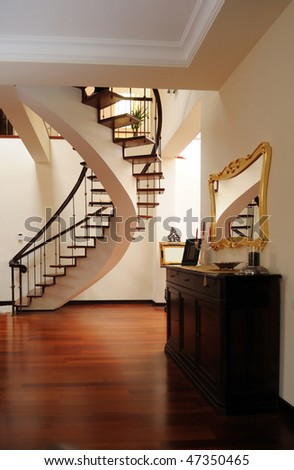 Beautiful classic foyer with interior stair, large mirror and wooden floor in a beautiful home interior - stock photo