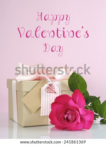 Beautiful classic kraft paper cardboard gift box with pale pink ribbon and rose, with Happy Valentines Day sample text greeting message. - stock photo