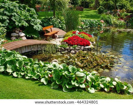 Beautiful classical design landscaped lush green blooming garden fish pond with water lily