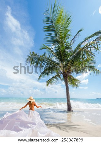Beautiful classy woman on the beach with white sarong. Thailand. - stock photo